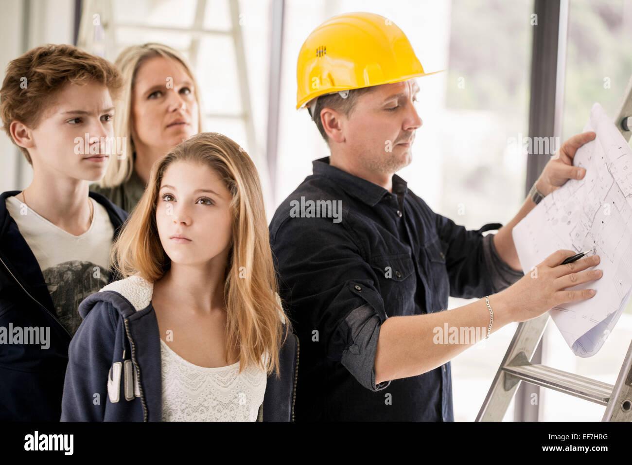 Ingénieur travaillant sur blueprint avec la famille Photo Stock