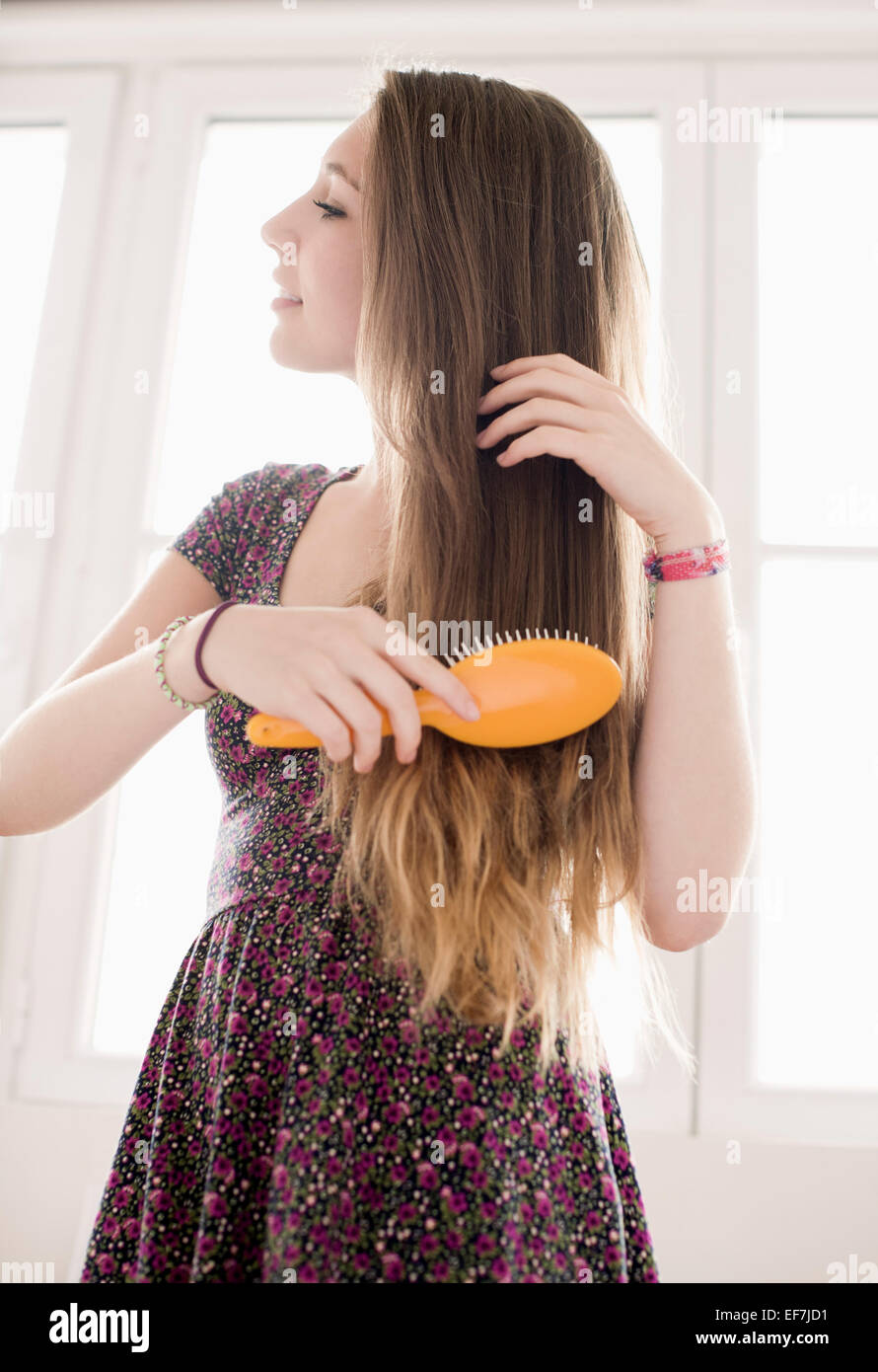 Teenage girl getting hair care avec brosse Photo Stock