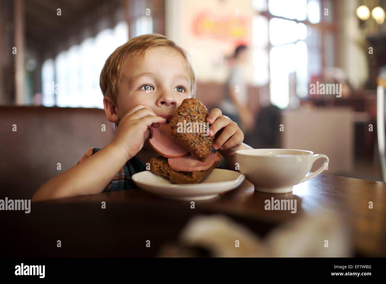 Petit enfant en train de déjeuner avec café et thé dans sandwich Photo Stock