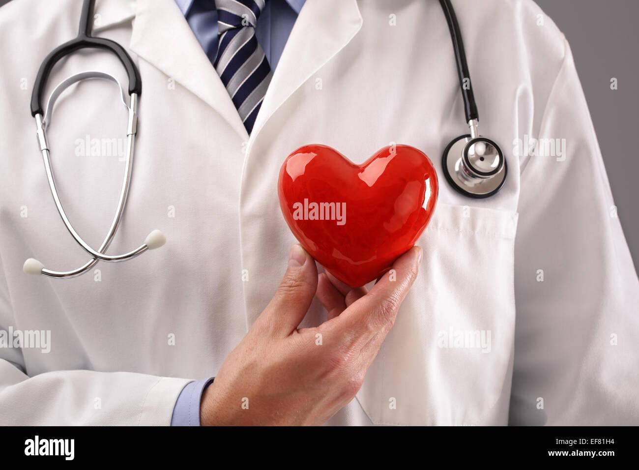 Doctor holding coeur contre poitrine Photo Stock