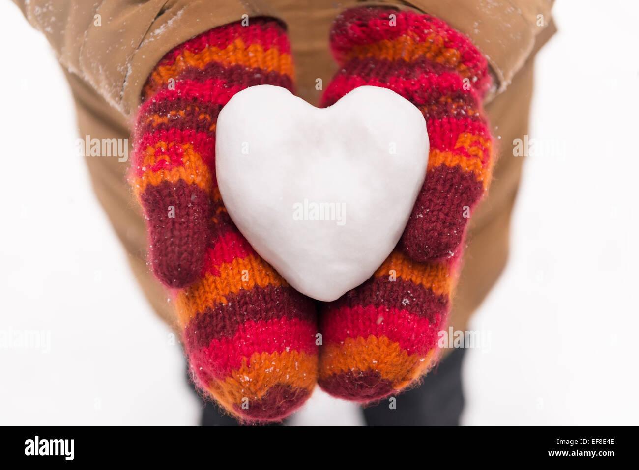 Les mitaines rouges de Femme tenant un cœur fait de neige, gros plan des mains, concept romantique Photo Stock