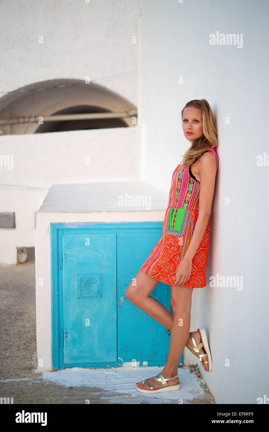 Woman leaning against wall Photo Stock