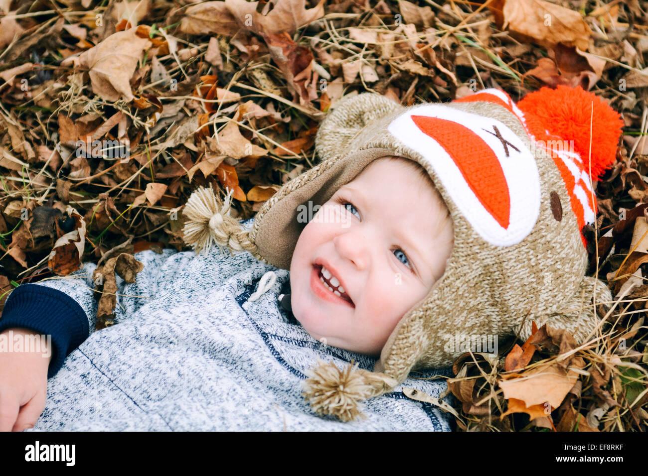 Garçon couché dans la pile de feuilles Photo Stock