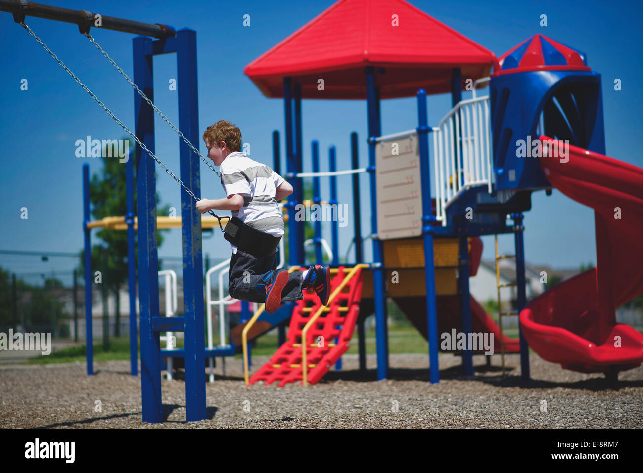 Boy (10-11) swinging sur swing sur aire Photo Stock