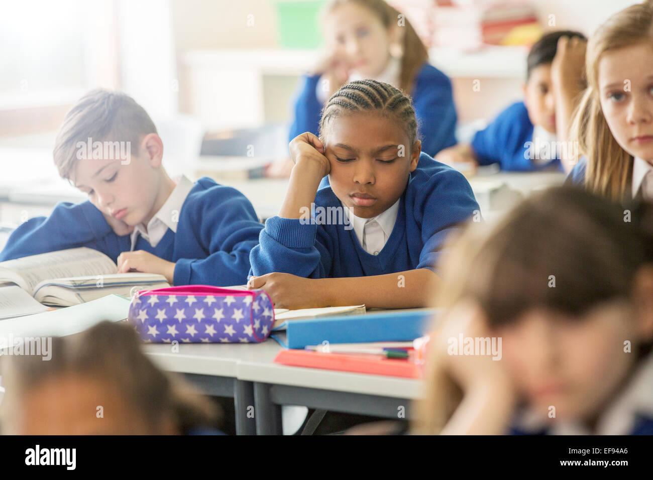 Les enfants de l'école élémentaire endormi et s'ennuient en classe Photo Stock