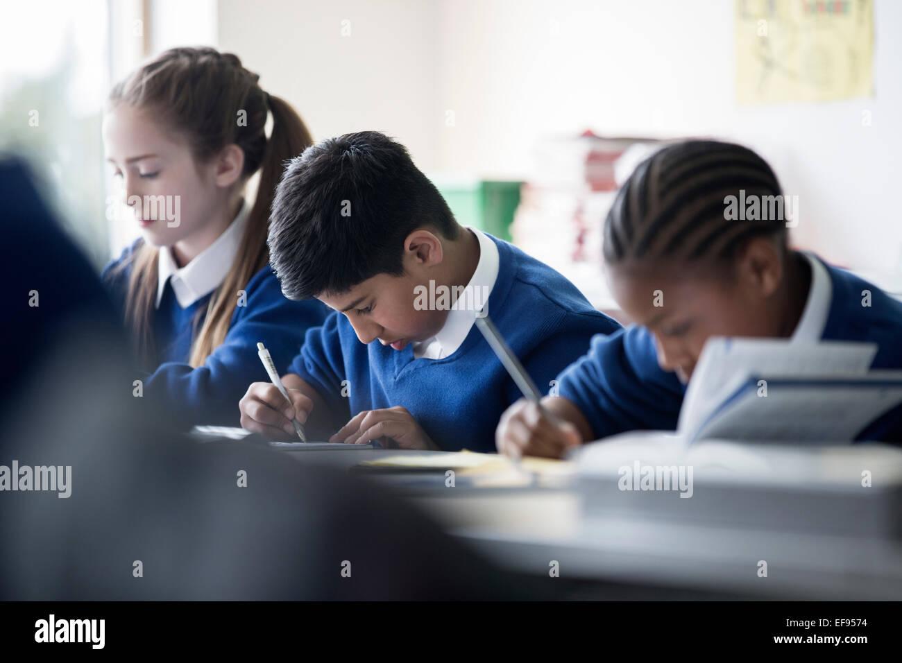 Les enfants de l'école élémentaire écrit en classe Photo Stock