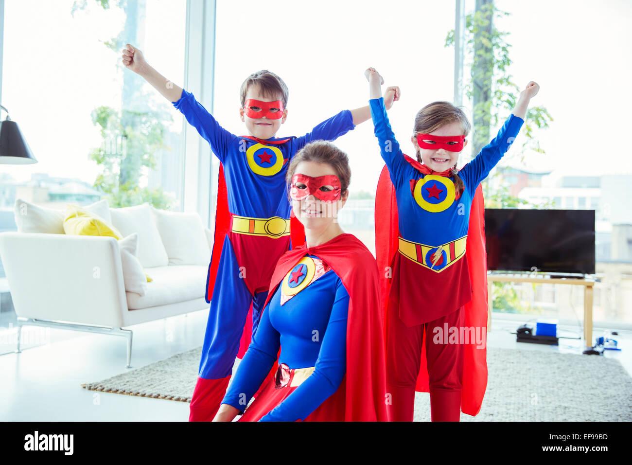 Les enfants de super-héros et mother smiling in living room Banque D'Images