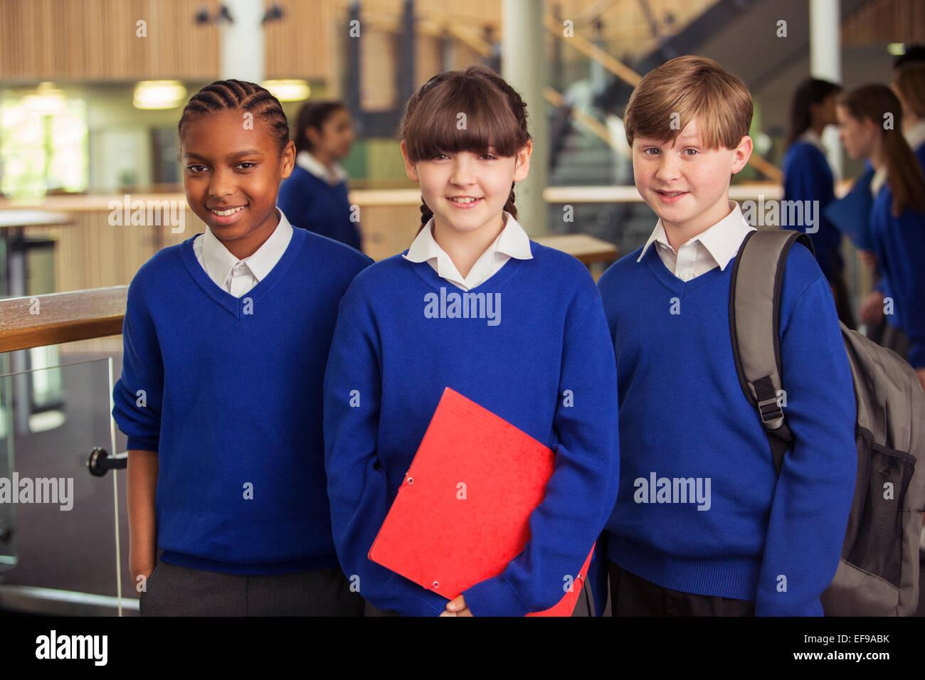 Portrait de trois enfants de l'école primaire portant des uniformes de l'école bleue dans le corridor Photo Stock