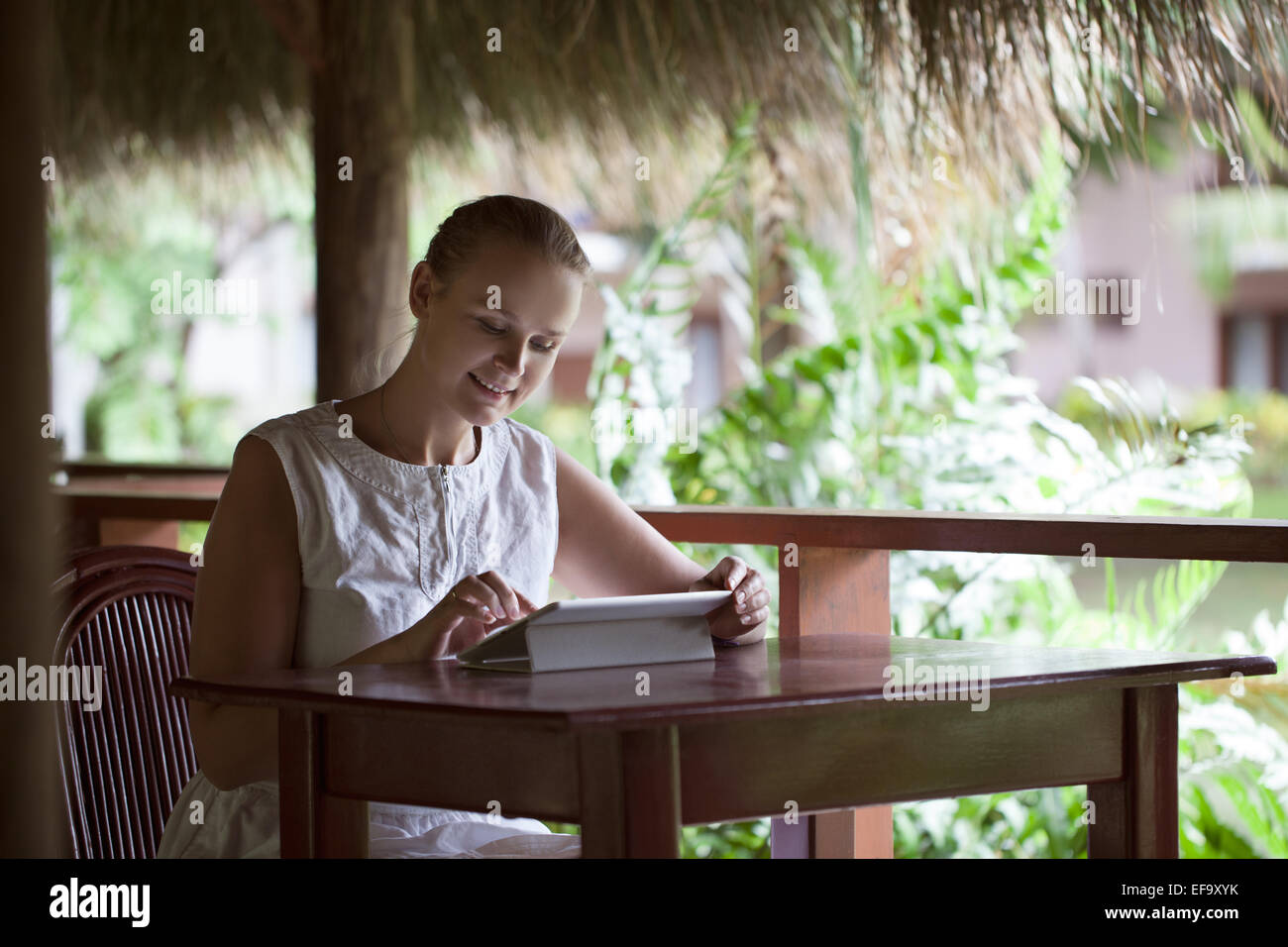 Smiling woman using tablet computer in cafe pendant ses vacances Photo Stock