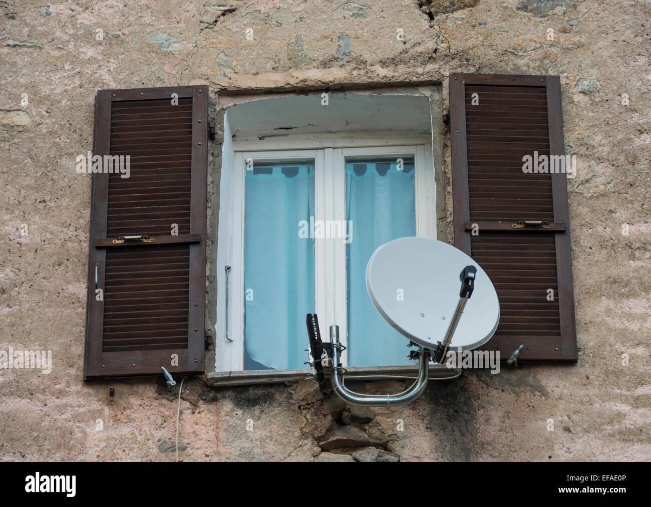 Fenêtre dans un bâtiment délabré avec la parabole et l'ouverture des volets, Corte, Corse, Photo Stock