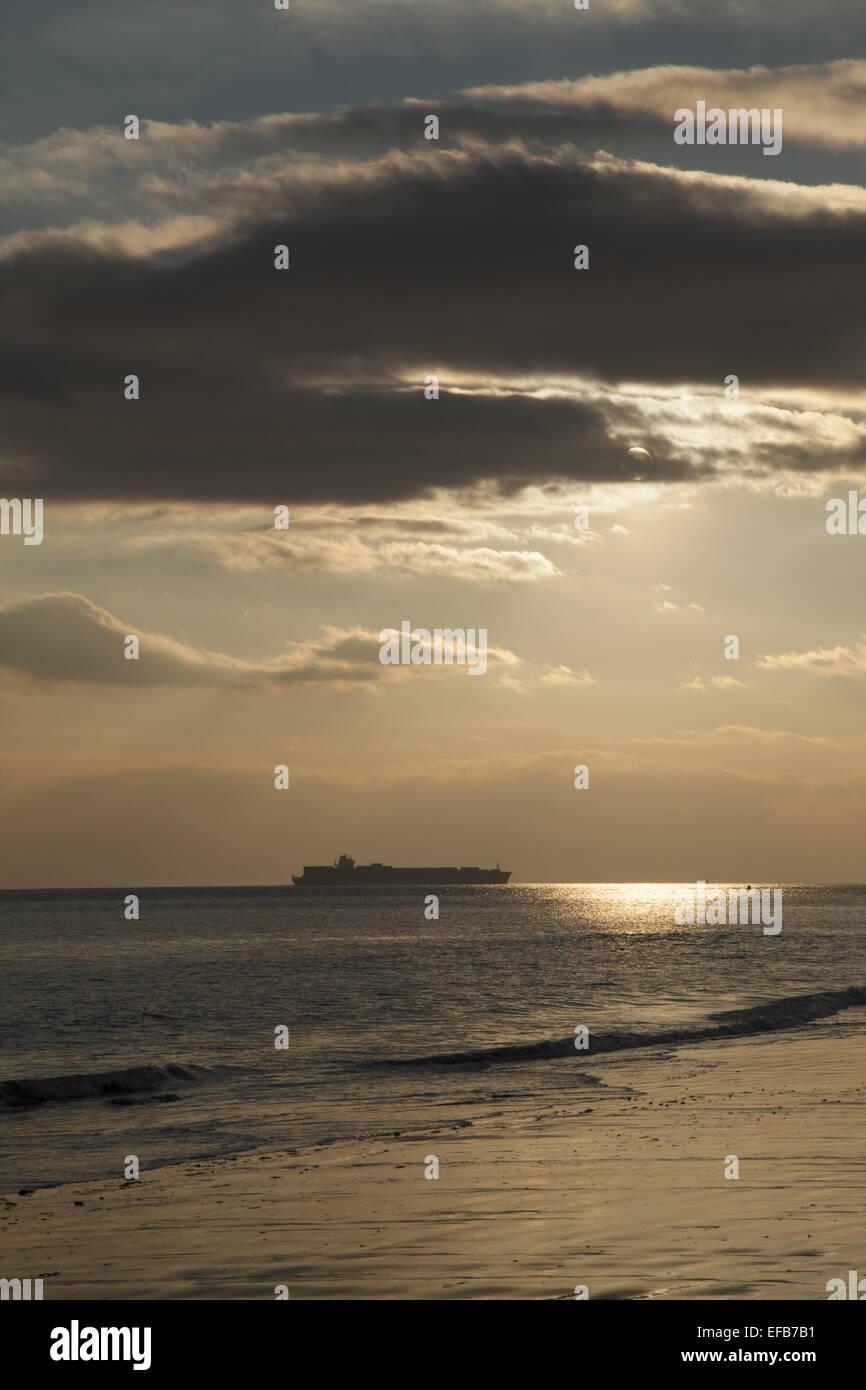 Freighter est assis sur l'horizon de la côte à Coney Island dans l'océan Atlantique près Photo Stock
