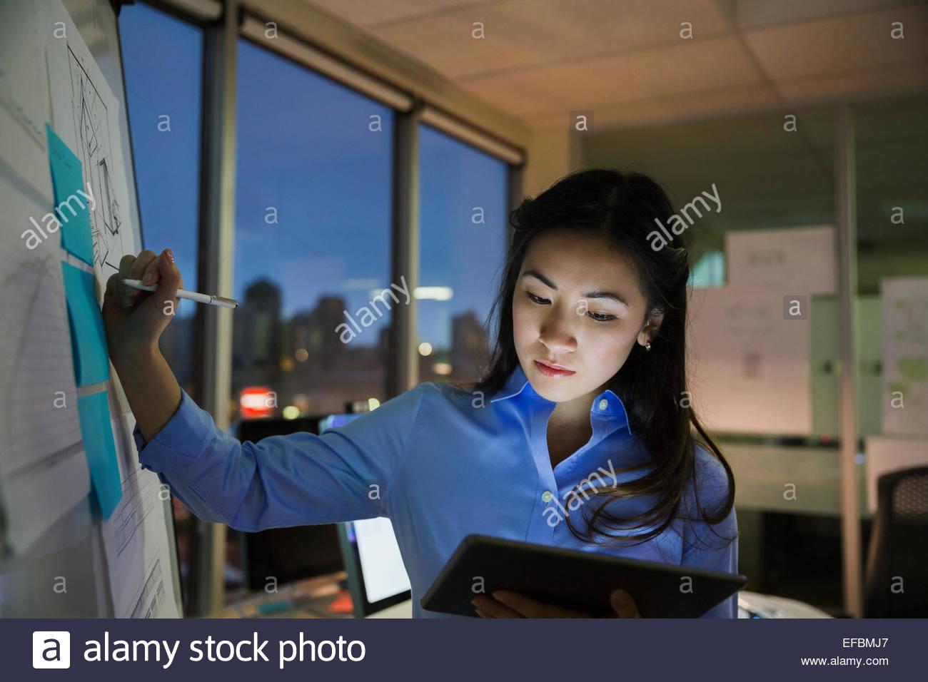 Businesswoman at whiteboard travailler tard dans la salle de conférence Photo Stock