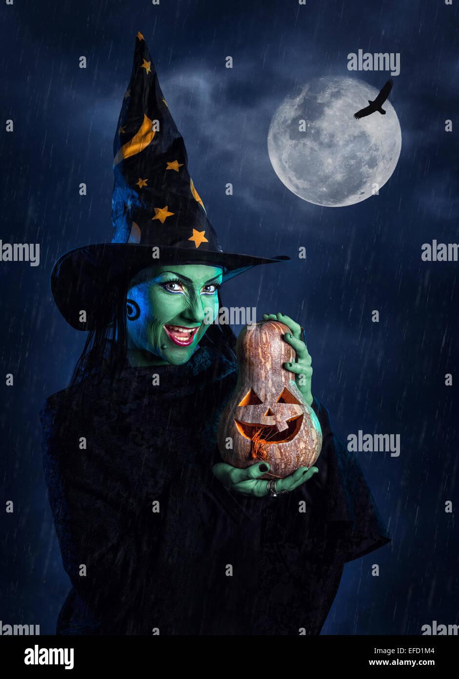 Sorcière avec peau verte tenue Halloween citrouille sculptée à lune et ciel noir avec de la pluie Photo Stock
