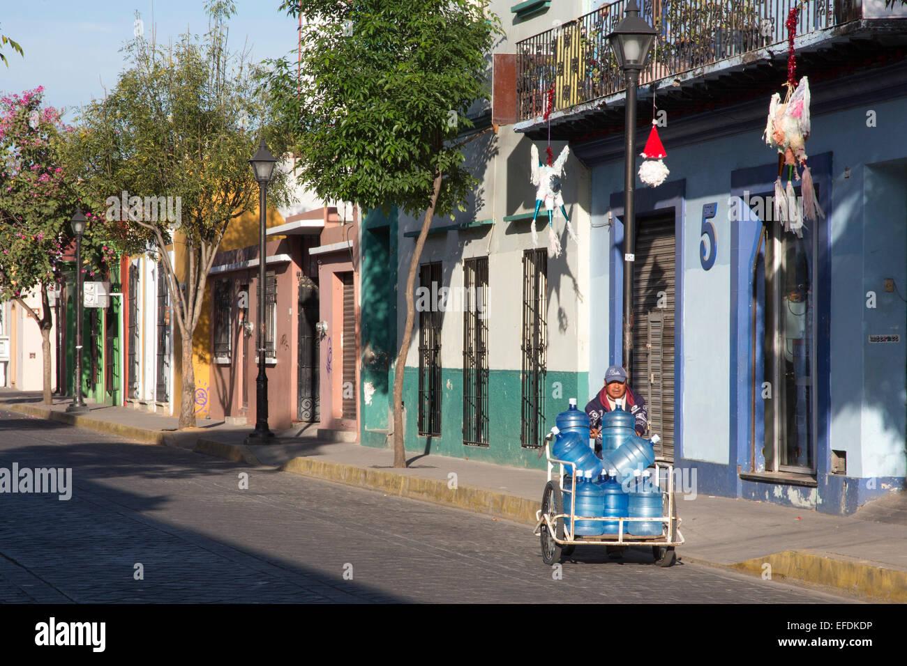 Oaxaca, Mexique - Un homme offre l'eau en bouteille avec un panier à la main. Photo Stock