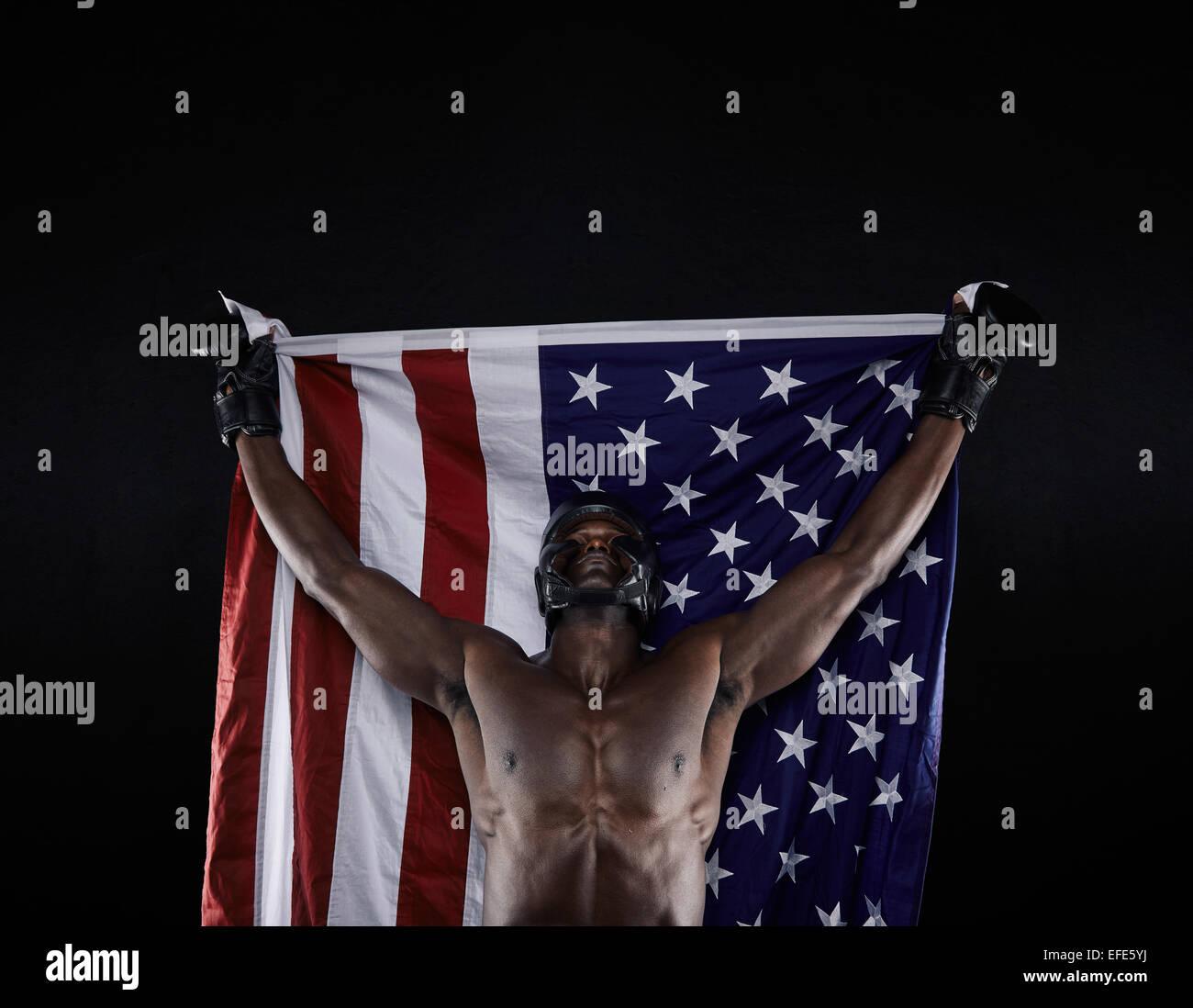 Jeune comptable boxer drapeau américain soulevé dans la victoire sur fond noir. Champion de boxe américain des succès Banque D'Images