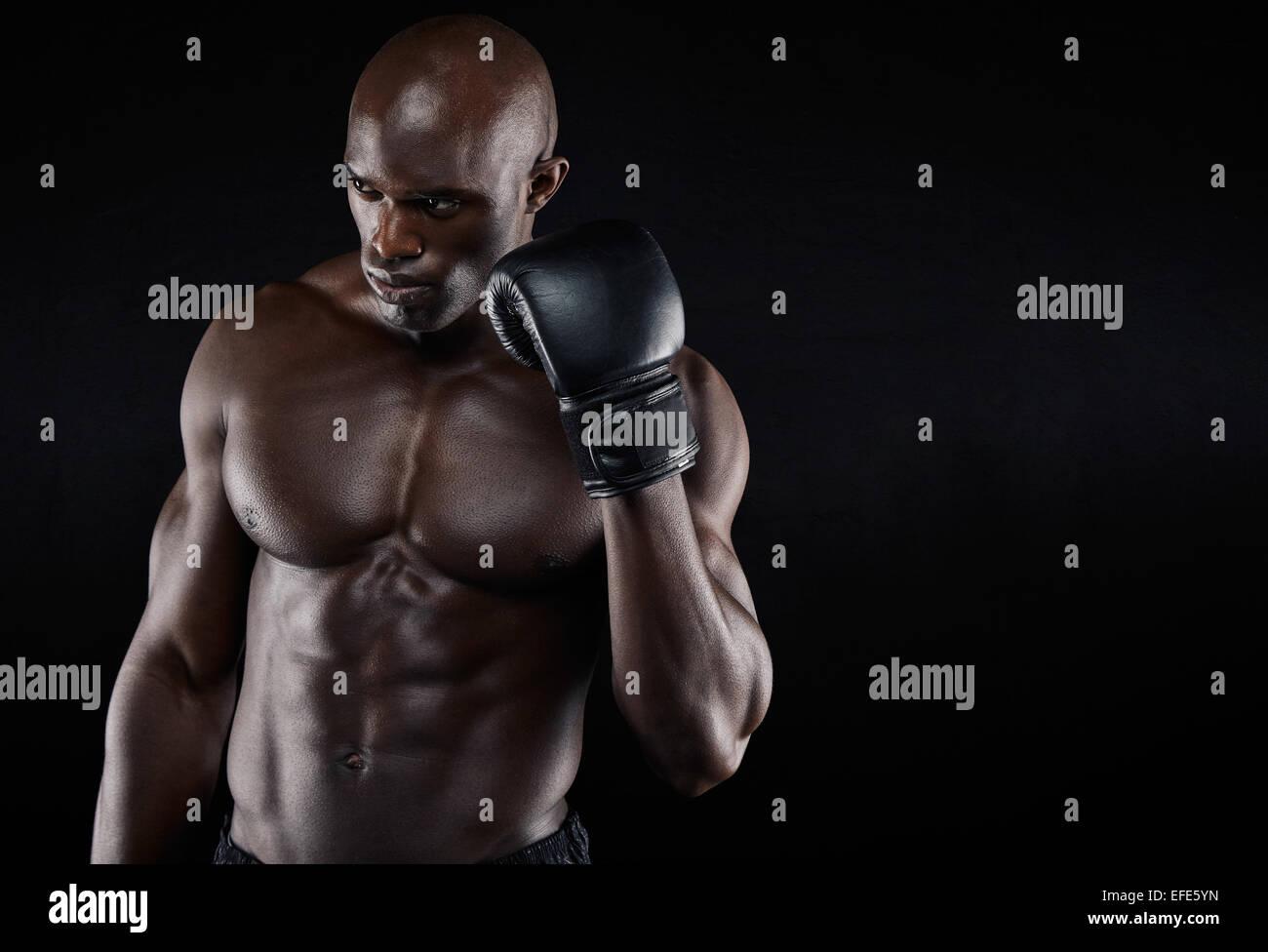 Portrait de jeunes déterminés pensant à son boxer se déplace sur fond noir. Male boxer pratiquer Photo Stock
