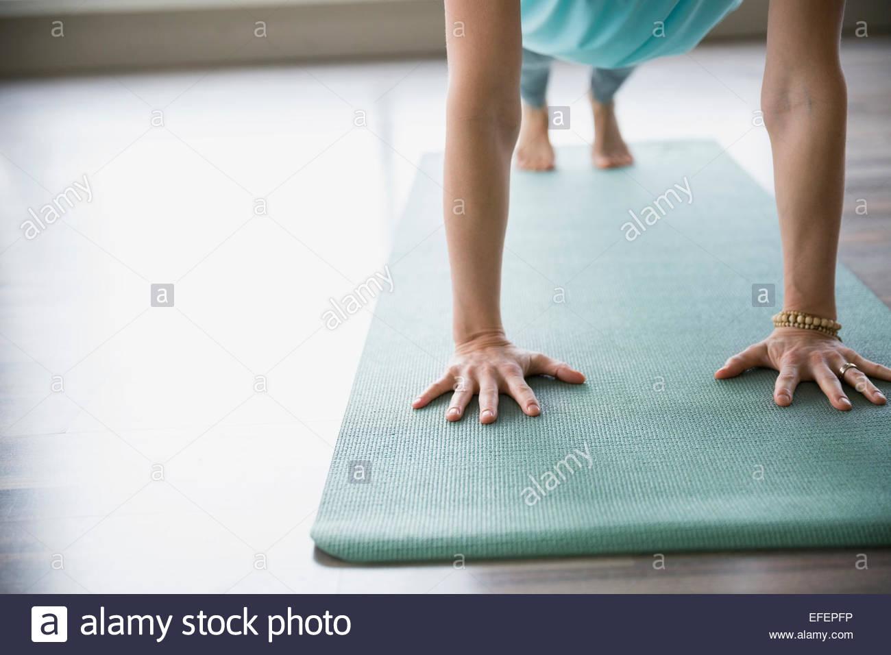 Woman practicing yoga on mat en planche Photo Stock