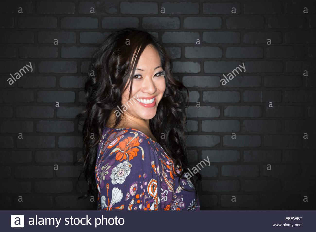 Portrait of smiling brunette wearing blouse à motifs Photo Stock