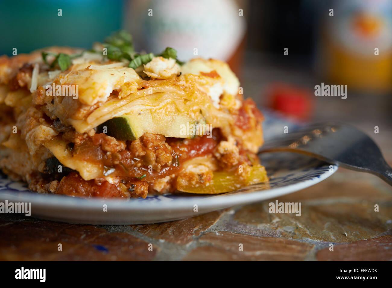 Lasagnes assis sur une assiette avec une fourchette qui sort. La photographie culinaire. Voir SID Photo Stock