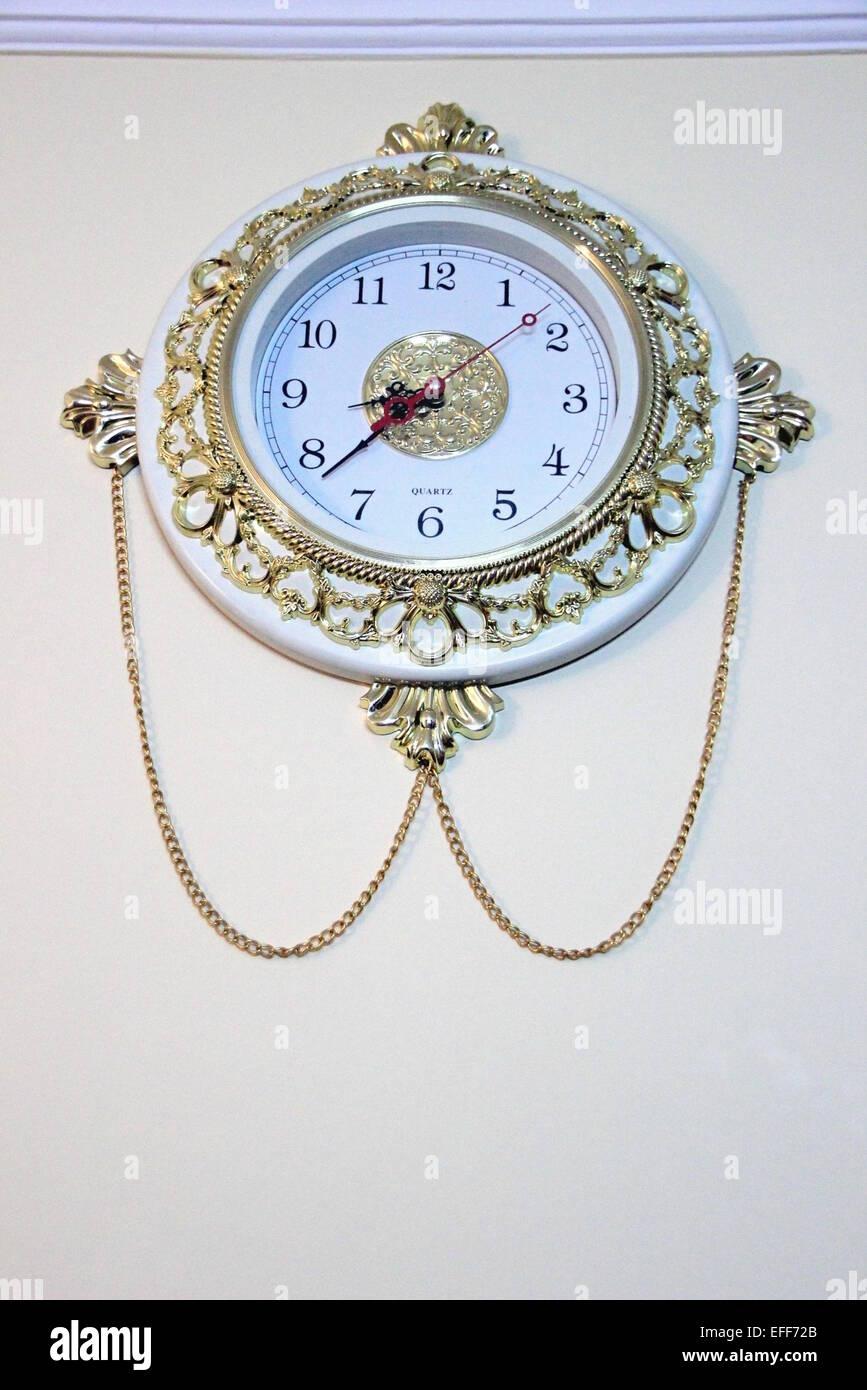Beau, riche, pièce d'ornement réveil accrochées sur mur peint de couleur claire. Photo Stock