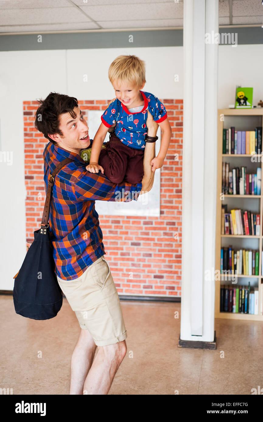 Père Fils ludique de levage à l'école primaire Photo Stock