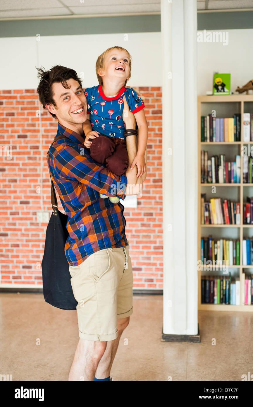 Portrait of happy father carrying son à l'école primaire Photo Stock