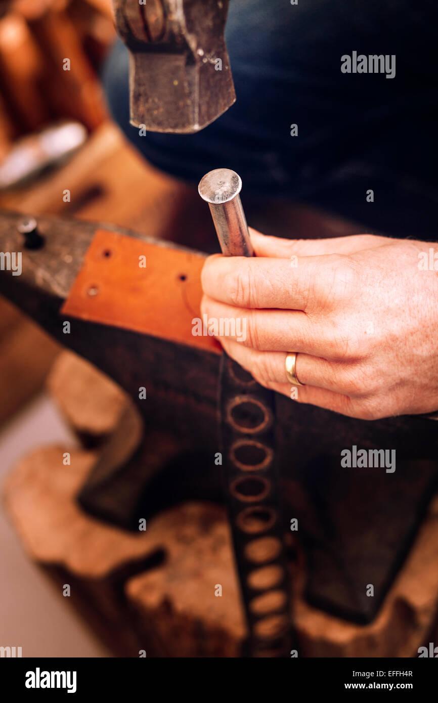 Travailleur de réaliser des trous de la courroie à l'aide d'un marteau à l'atelier Photo Stock