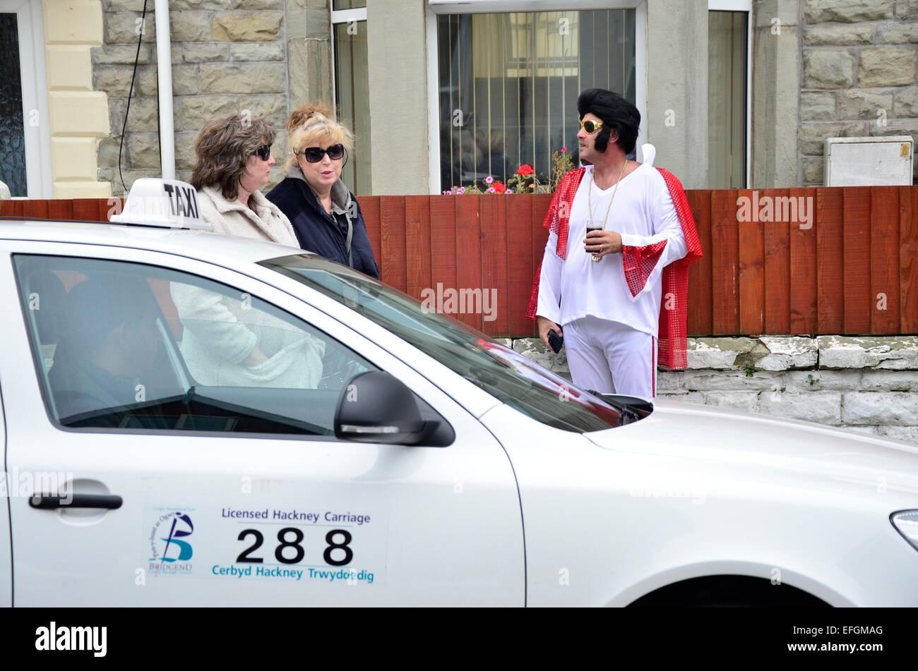 Elvis Impersonator debout à côté de deux femmes et d'un taxi à l'Elvis Festival (The Photo Stock