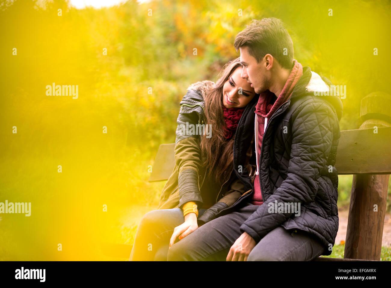 Couple aimant à l'automne assis sur un banc de parc Photo Stock