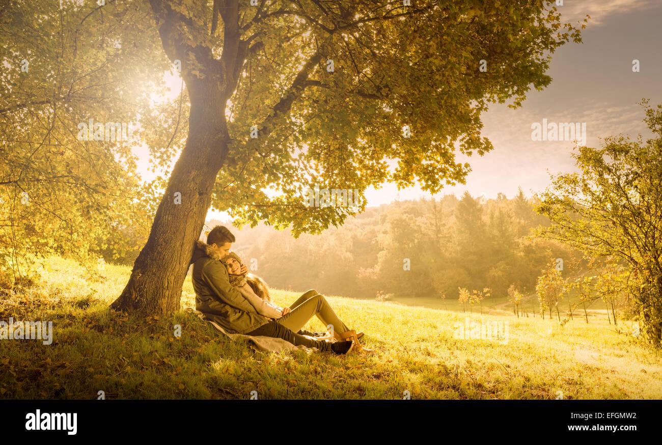 Couple d'amoureux sous un grand arbre dans le parc en automne Photo Stock