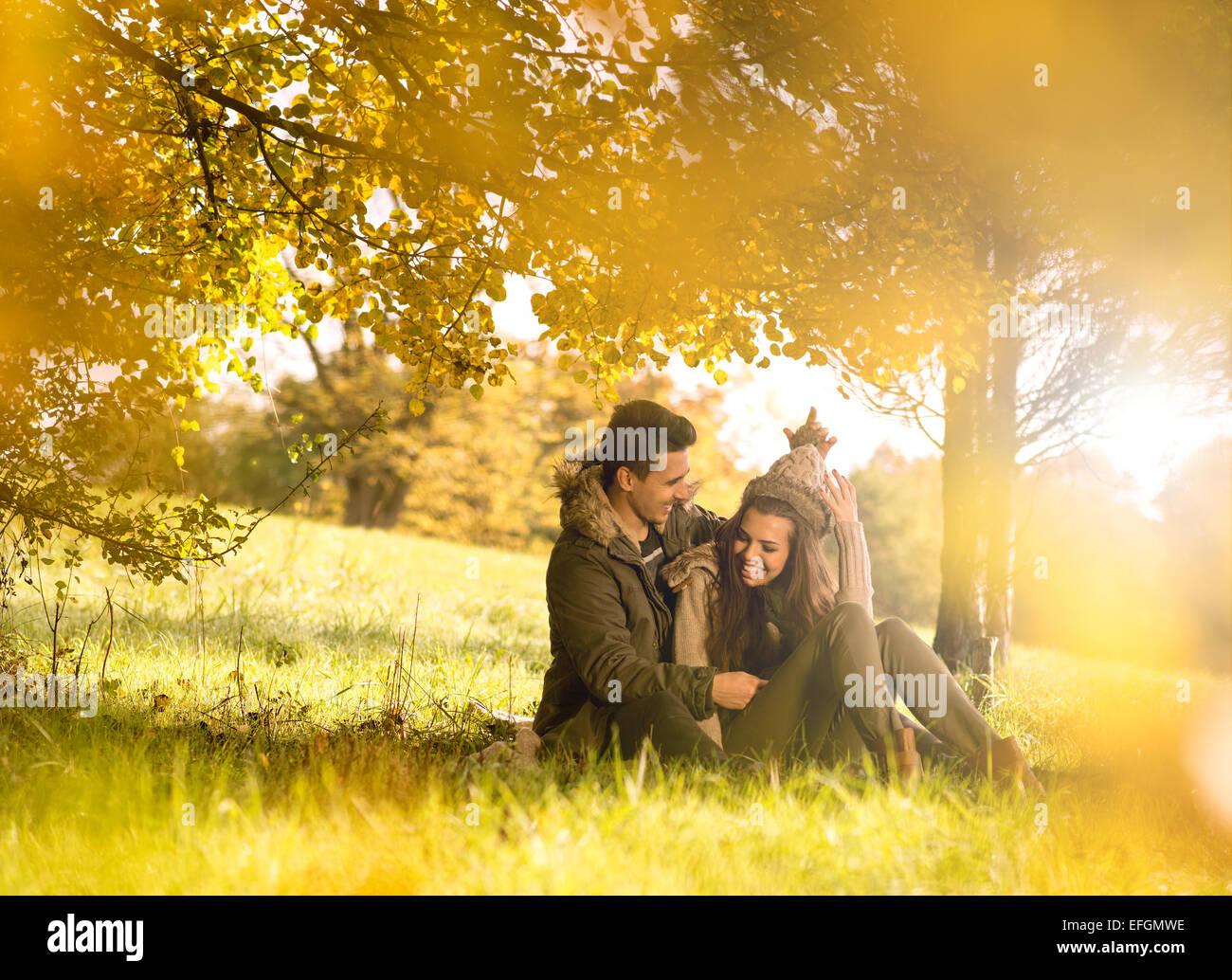 Couple heureux sous l'arbre dans le parc de l'automne Photo Stock