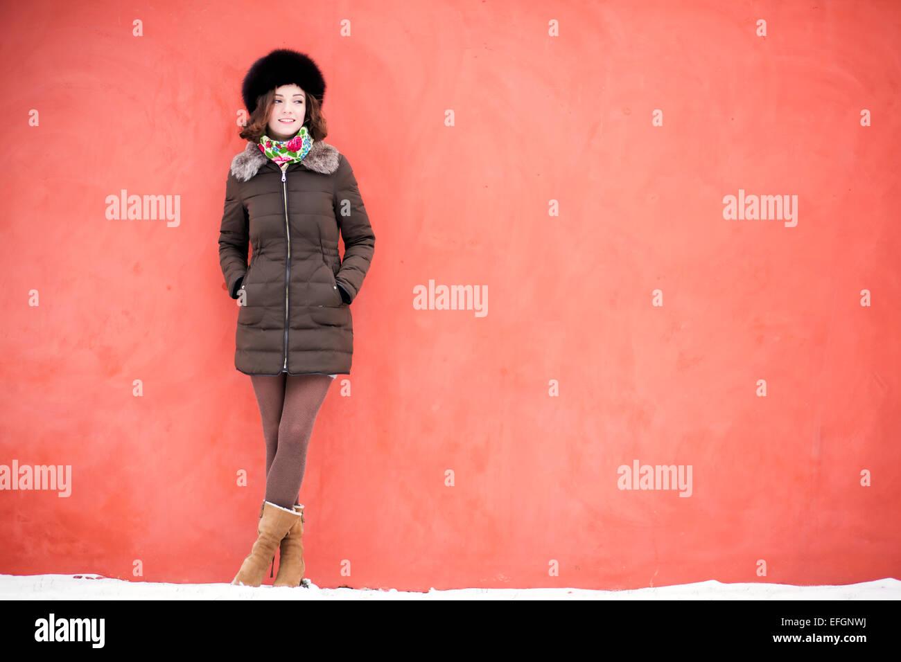 Femme est de bonne humeur près du mur rouge Photo Stock