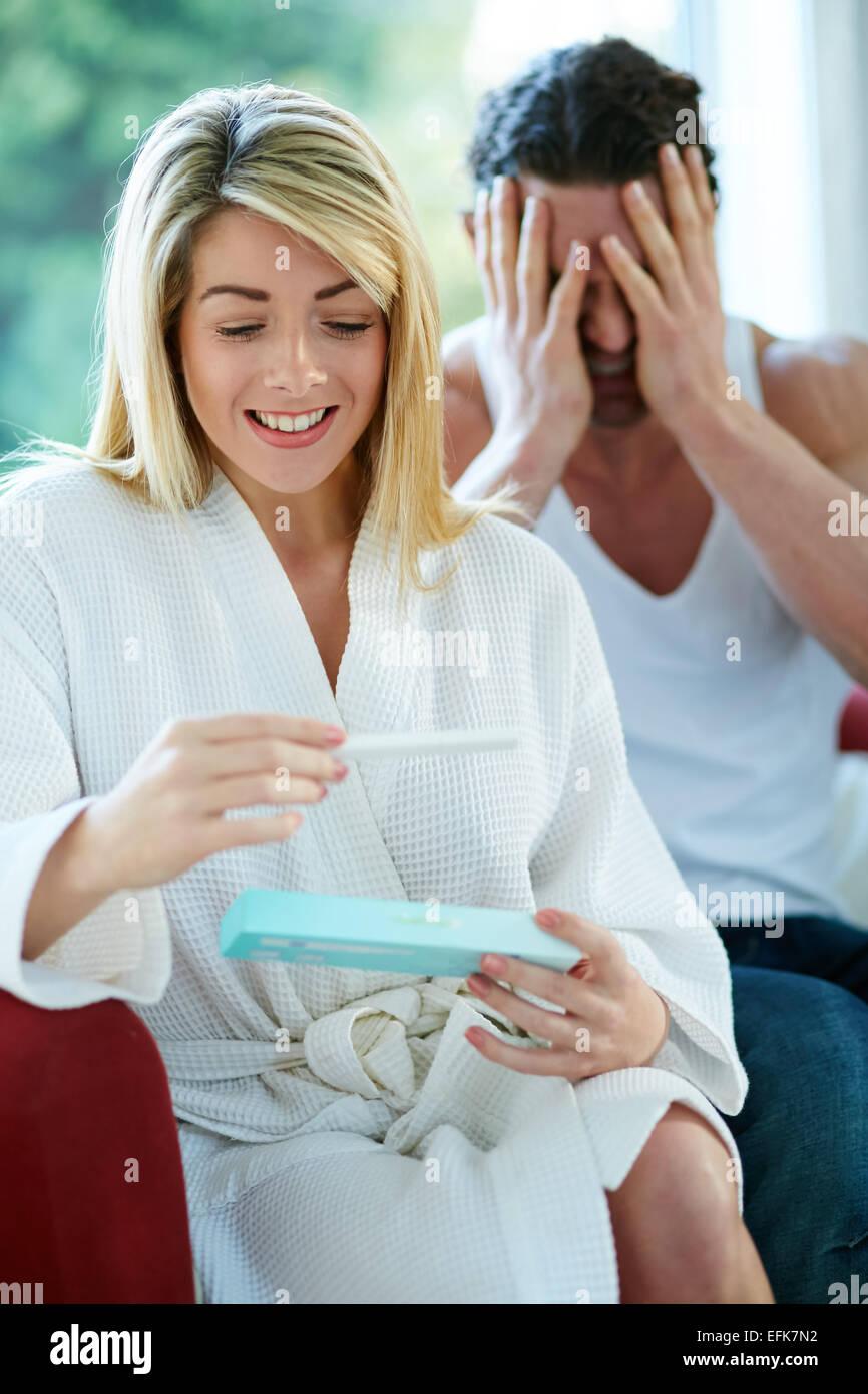 Happy girl trouver qu'elle est enceinte avec colère man in background Photo Stock