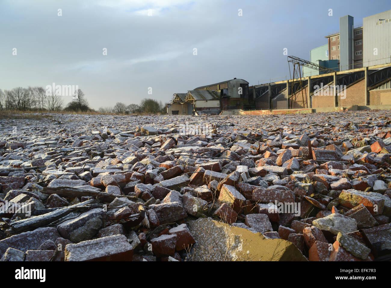 Des tas de gravats sur les terrains vagues et bâtiment de l'usine couvert par neige de l'hiver près Photo Stock