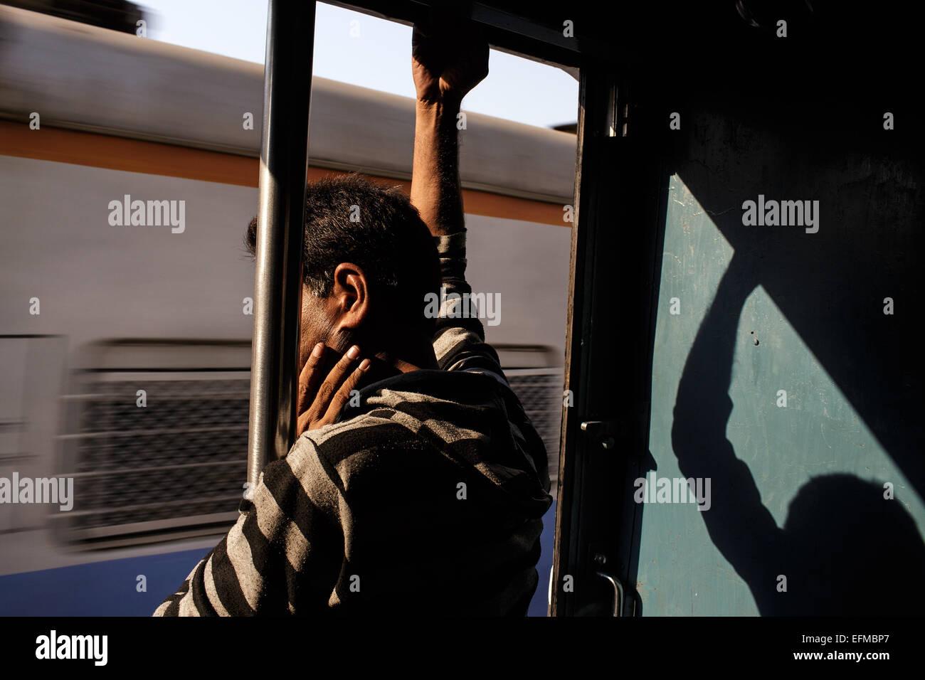 Un homme travaille sur un train de banlieue de Mumbai, Inde Banque D'Images