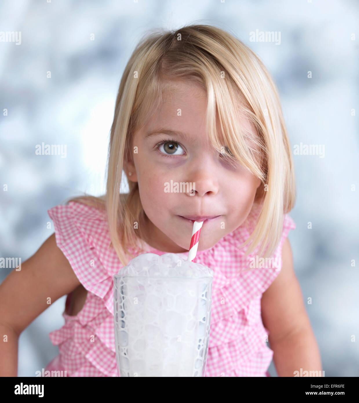 Portrait of cute female toddler faisant des bulles dans le verre de lait Banque D'Images
