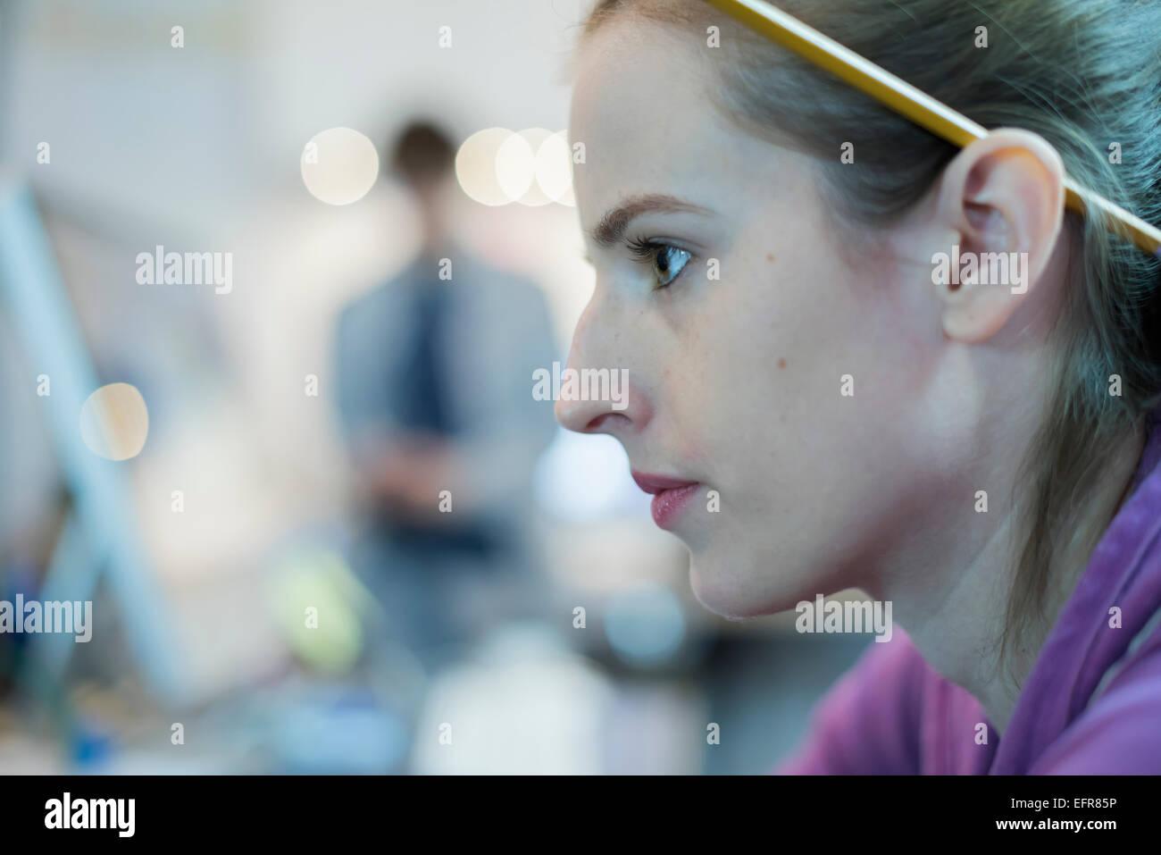 Une jeune femme avec un crayon derrière l'oreille, à un atelier de réparation d'ordinateur. Photo Stock
