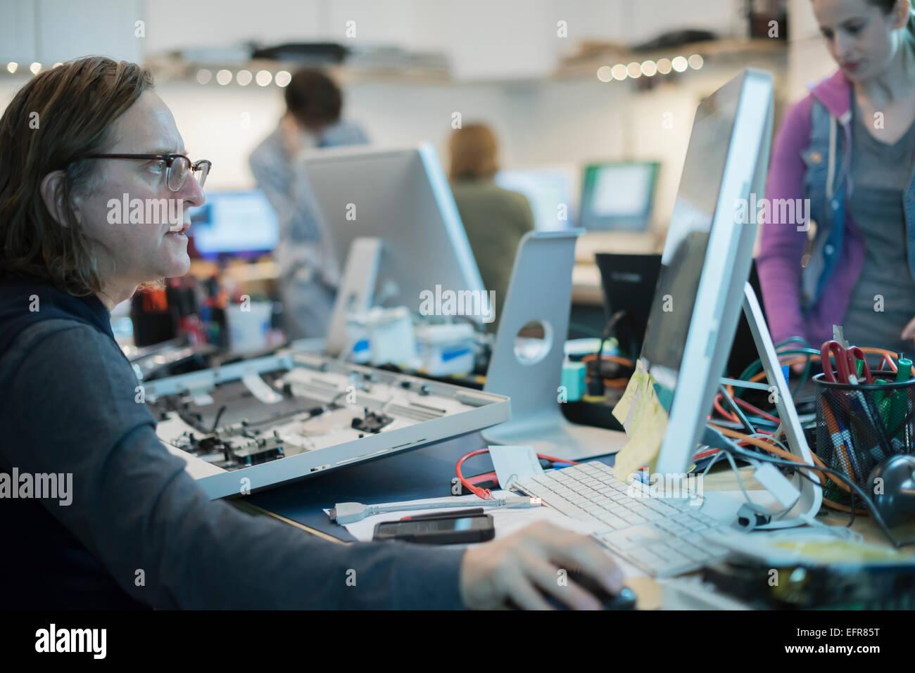 Un homme assis à un ordinateur, regarder l'écran. Atelier de réparation d'ordinateur. Photo Stock
