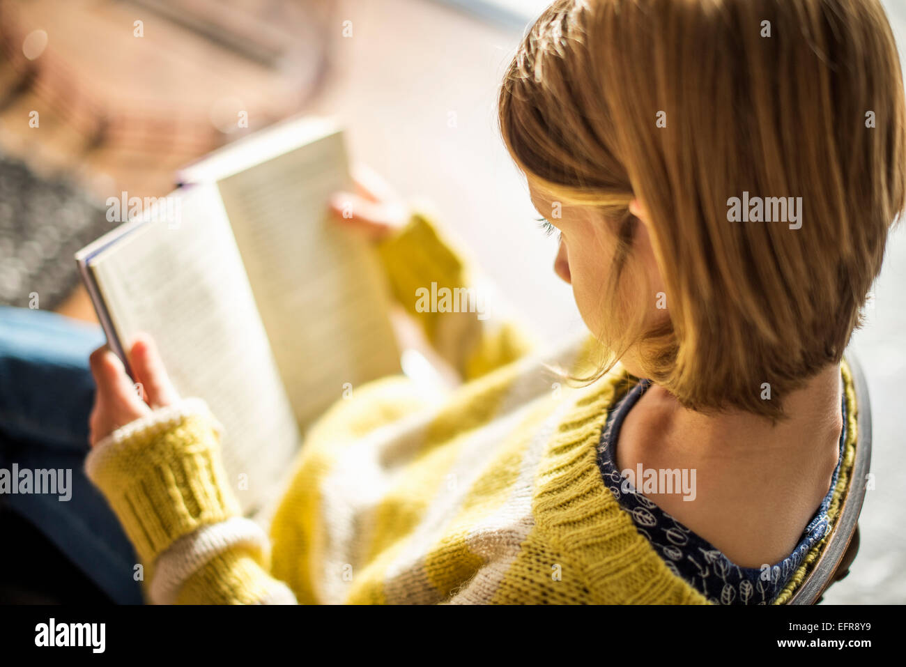 Portrait d'une fille blonde dans un cavalier jaune assis sur une chaise, lisant un livre. Photo Stock