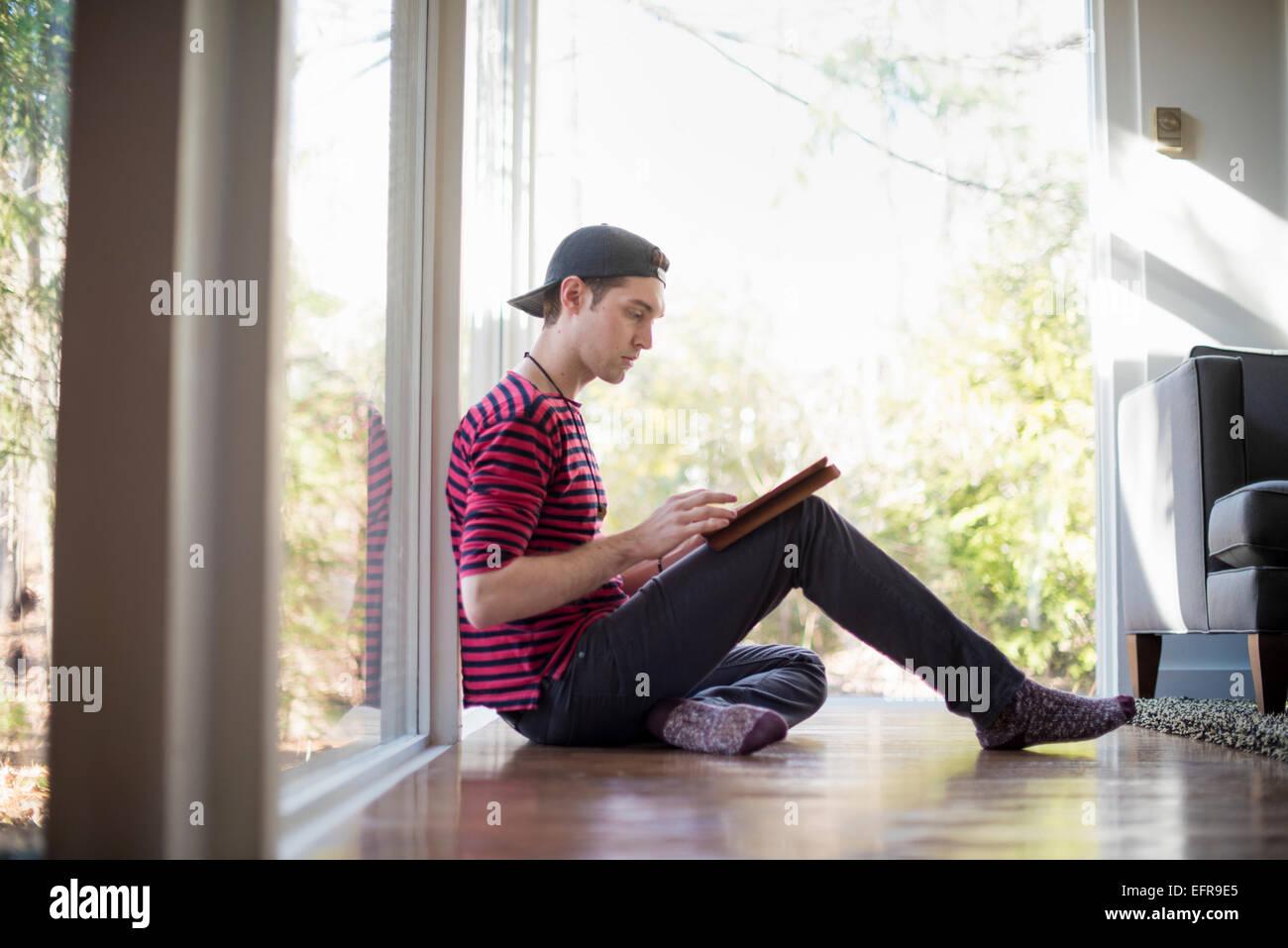 Homme portant une casquette de baseball en arrière, assis sur le plancher d'une salle de séjour, regarder Photo Stock