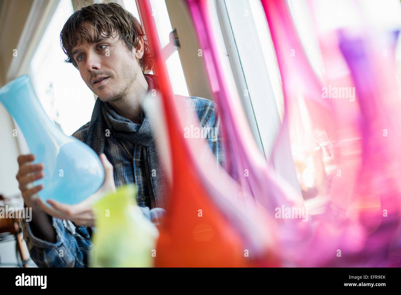 Homme debout dans un salon, tenant un vase de verre bleu. Vases rouges et roses au premier plan. Photo Stock