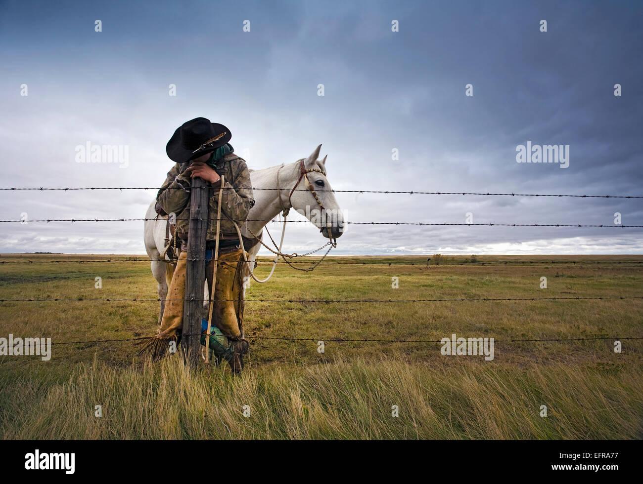 Un cowboy debout appuyée sur un poteau de clôture sur la plage. Un cheval gris derrière lui. Banque D'Images