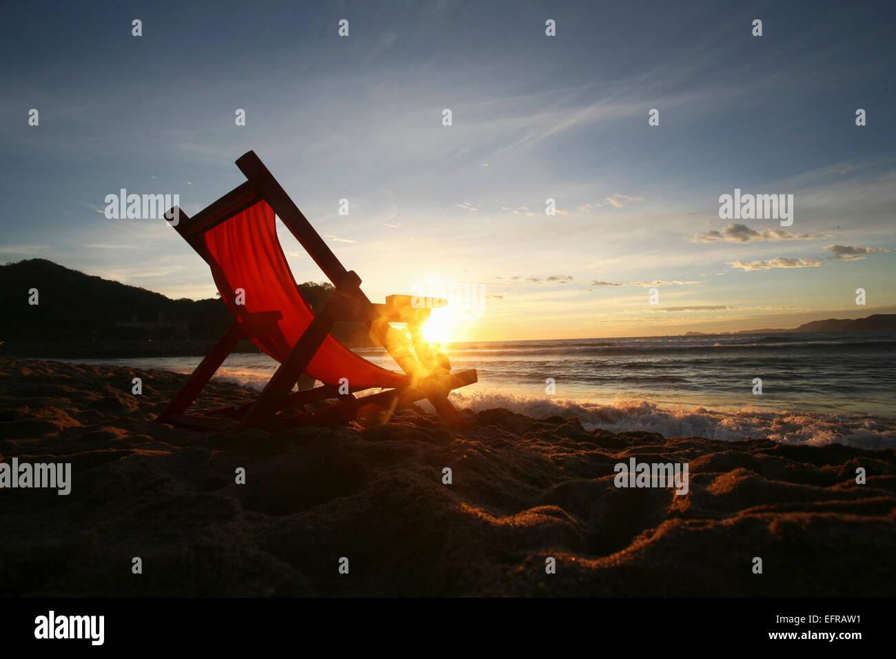 Une chaise sur le sable face à l'eau. Photo Stock