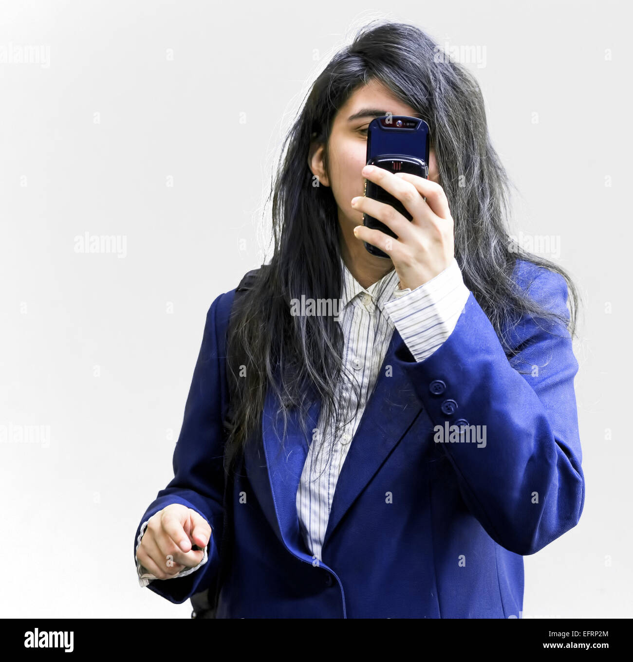Latina teen girl holding cellphone a fait à huis clos Photo Stock