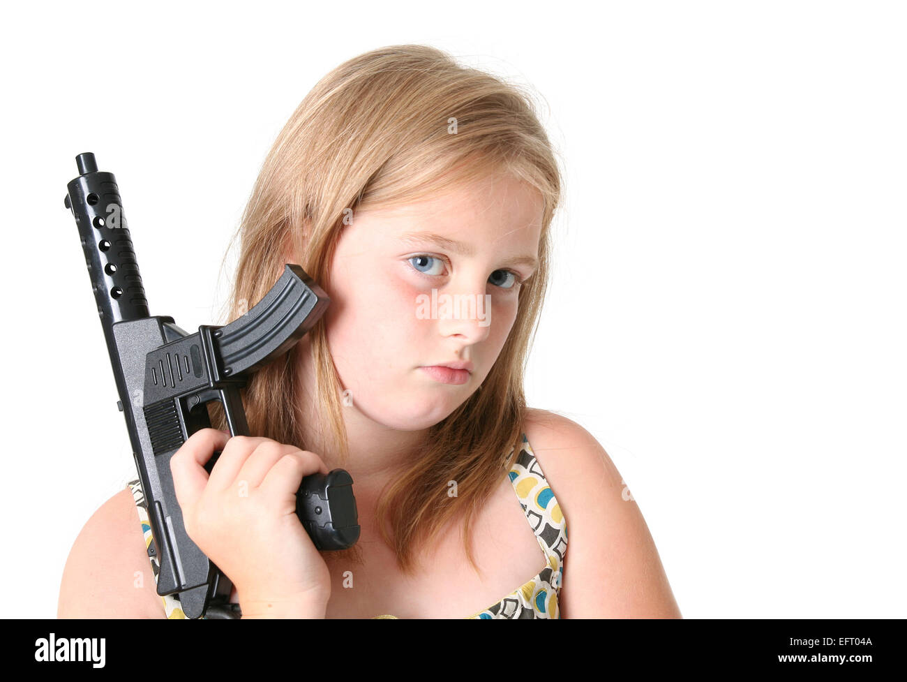 Girl with gun isolé sur blanc. enfant ou adolescent en robe