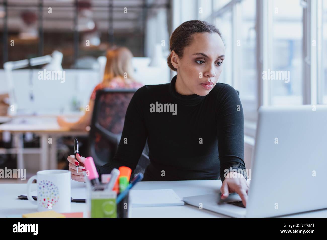 Image de jeune femme travaillant sur un ordinateur portable tout en étant assis à son bureau dans un bureau Photo Stock