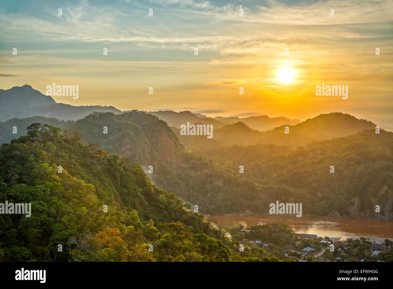 Coucher de soleil sur les collines couvertes de jungle luxuriante avec la rivière Beni visible à Rurrenabaque, Photo Stock
