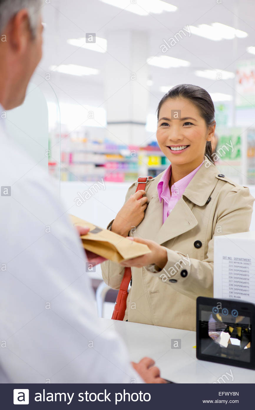 La clientèle féminine de sourire et de faire un achat en pharmacie Photo Stock