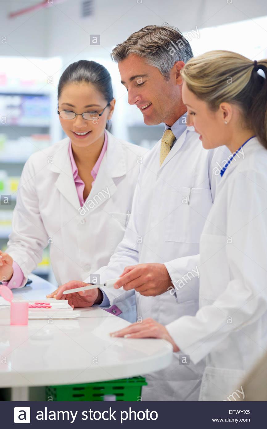 Pharmacien, en comptant les médicaments, sourire et parler à ses collègues en pharmacie Photo Stock