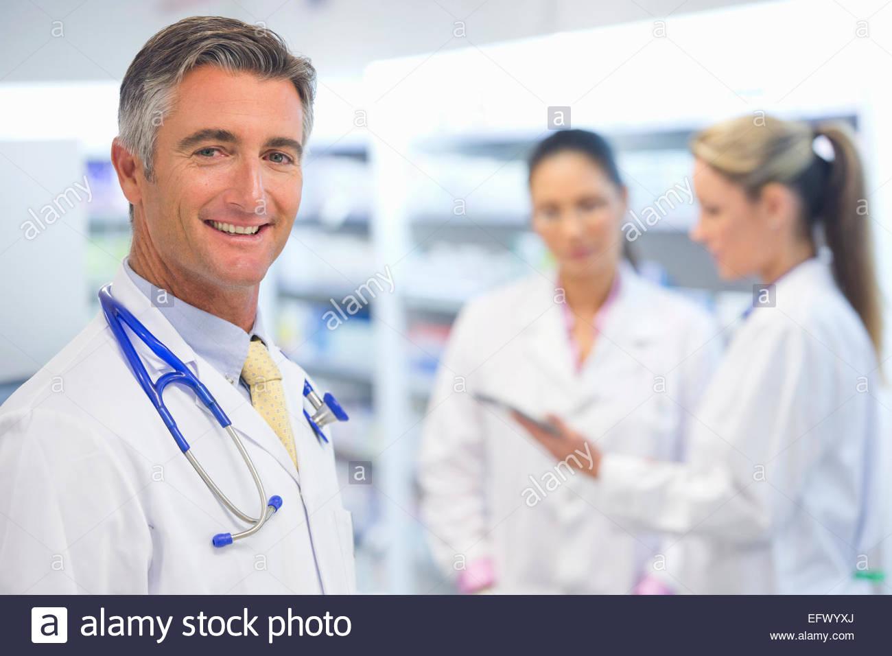 Médecin, wearing stethoscope, smiling at camera, avec des collègues en arrière-plan Photo Stock